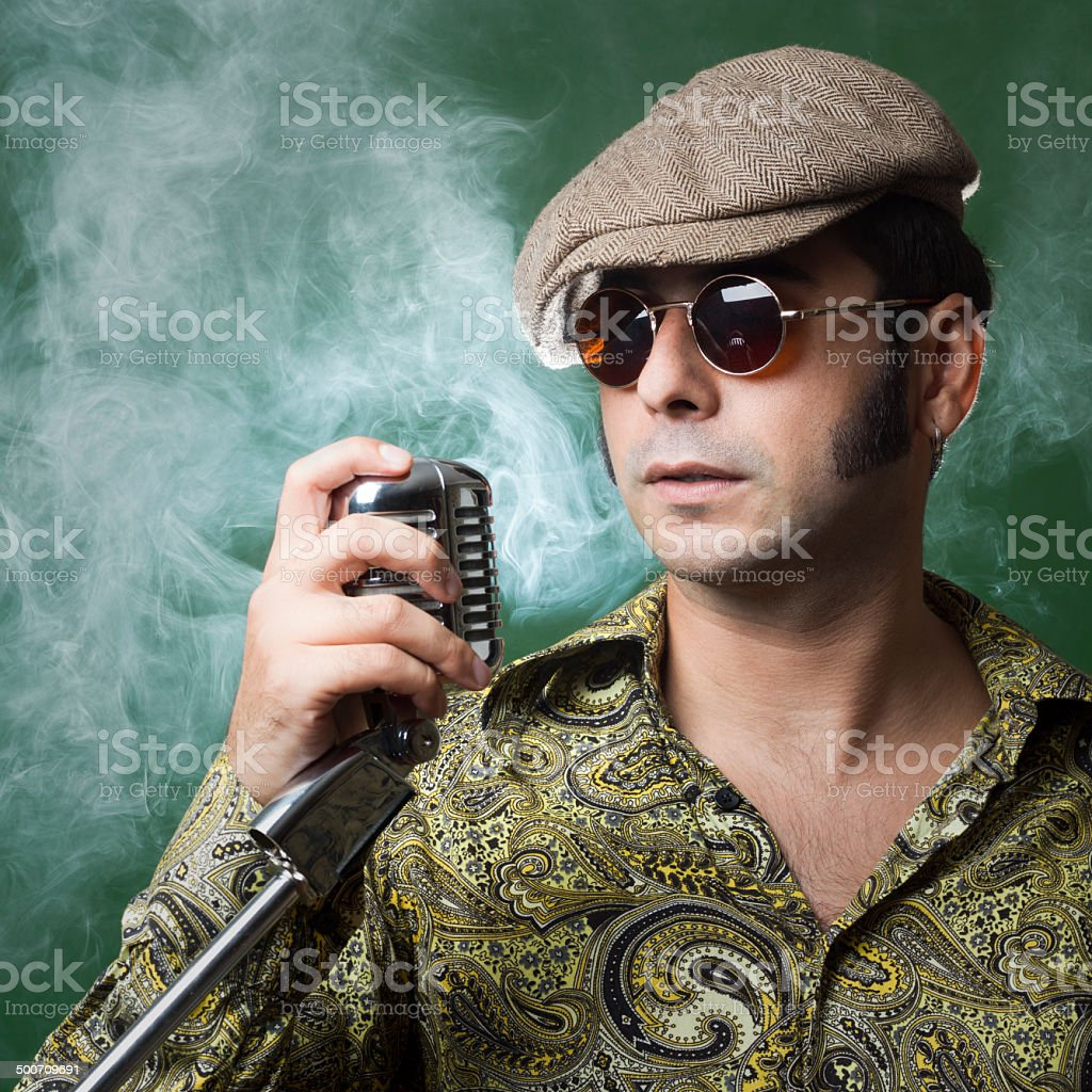 Funky adult man in 1970s style singing on microphone stock photo
