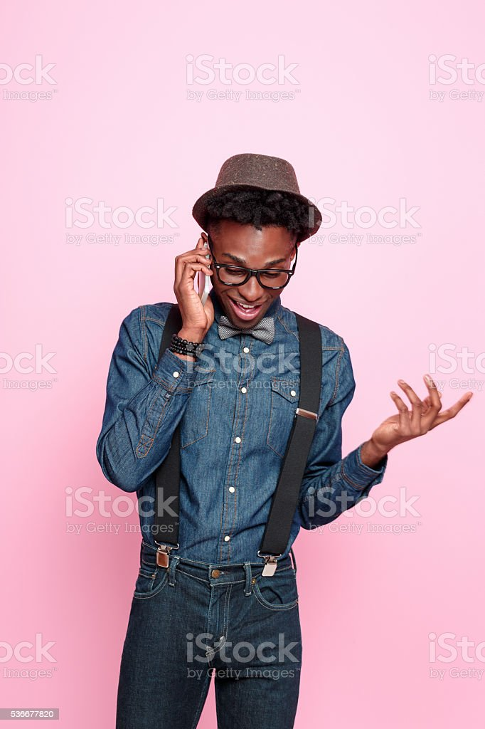 Funky afro american guy talking on smart phone stock photo