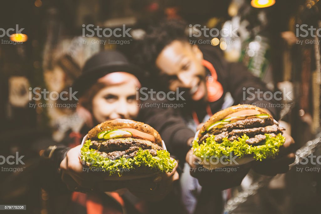 Funky friends in fast food restaurant, holding burgers stock photo