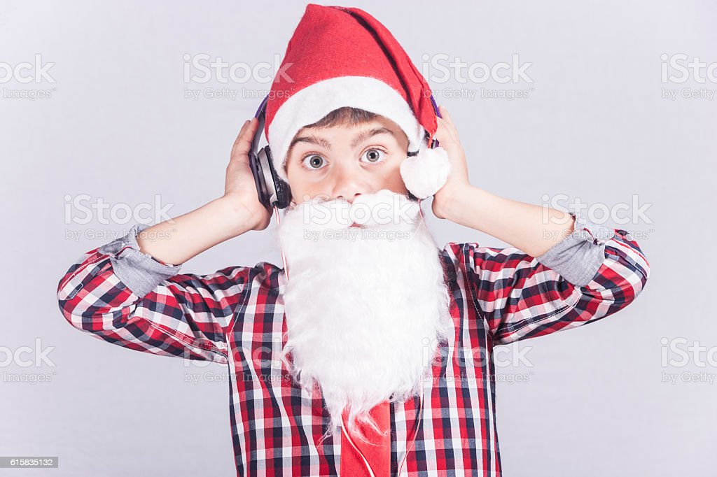 Funky little Santa Claus listening to music stock photo