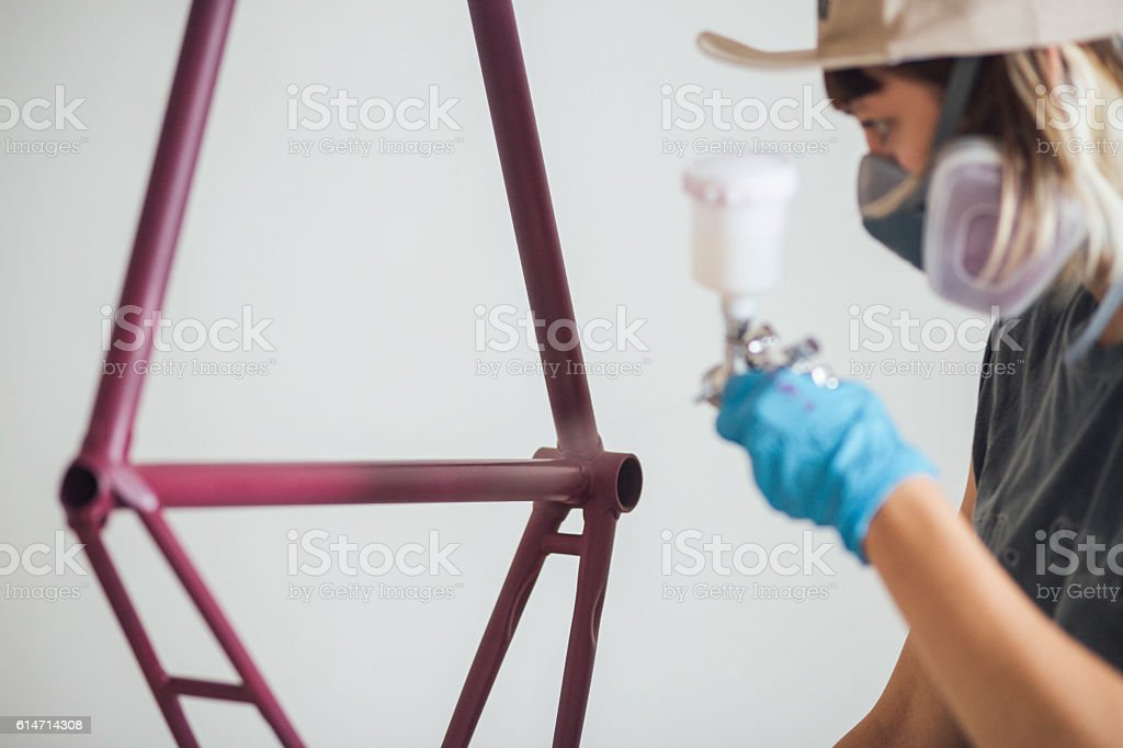 Funky modern woman painting bicycle frame stock photo