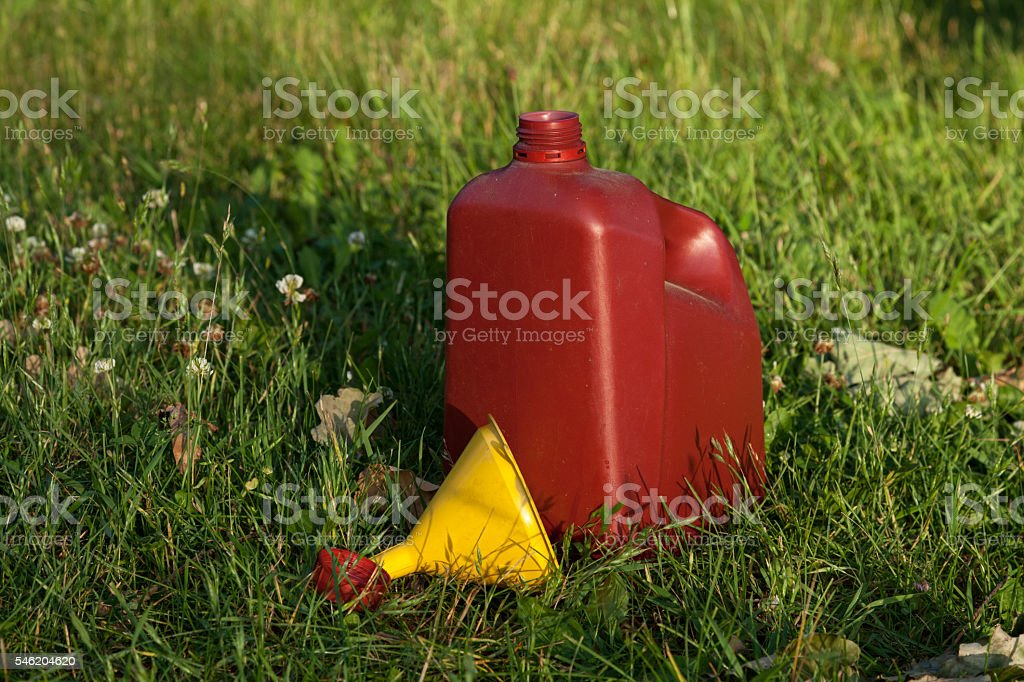 Funnel lying on the grass near open oil can stock photo