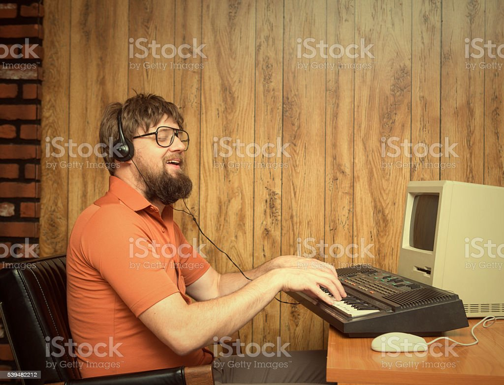 Funny 1980s retro man playing synth keyboard on computer stock photo