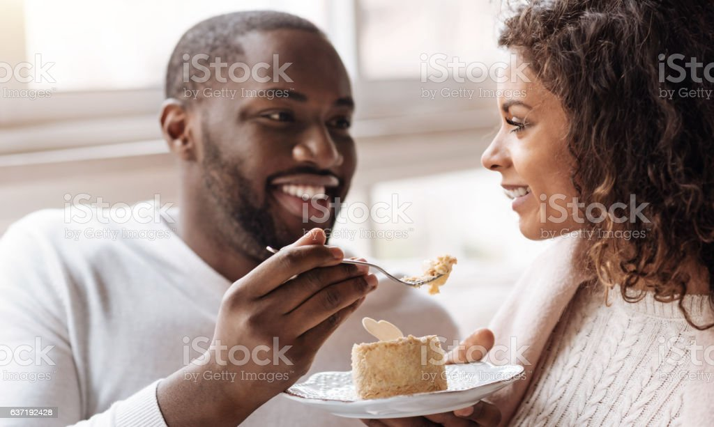 Funny African American couple enjoying the dessert in the cafe stock photo