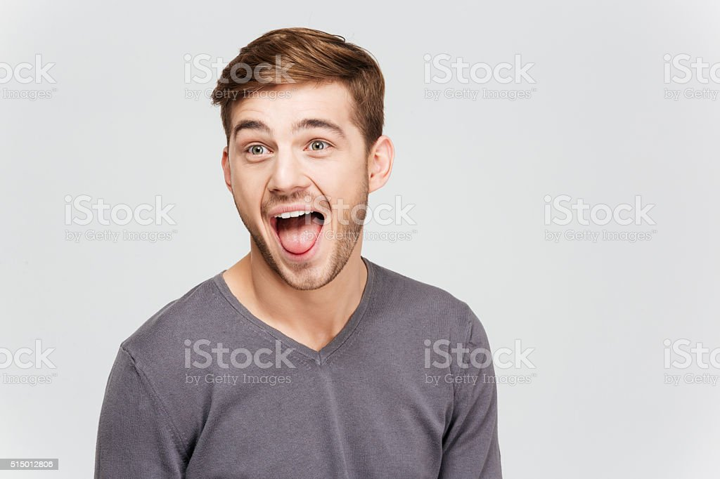 Funny amusing young man in grey pullover screaming stock photo