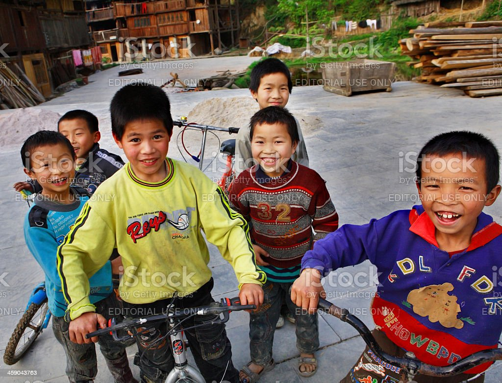 Funny Asian children from rural areas of China, ride bikes. stock photo