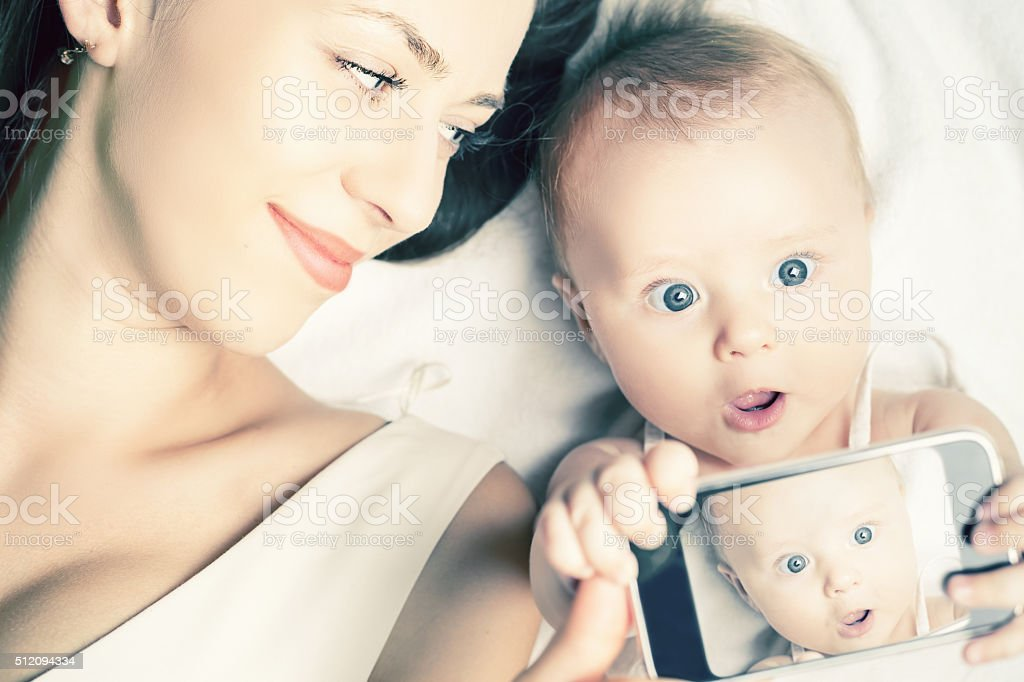 Funny baby and mother make selfie on mobile phone stock photo
