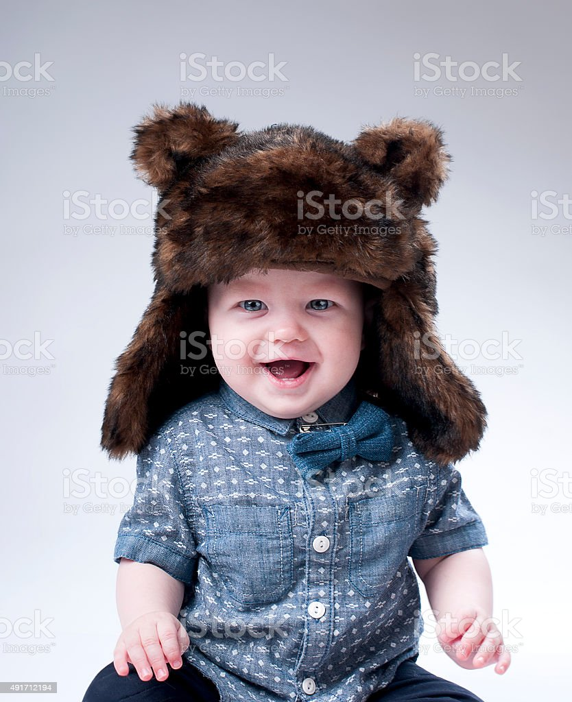 Funny baby boy  in a  brown fur hat . stock photo