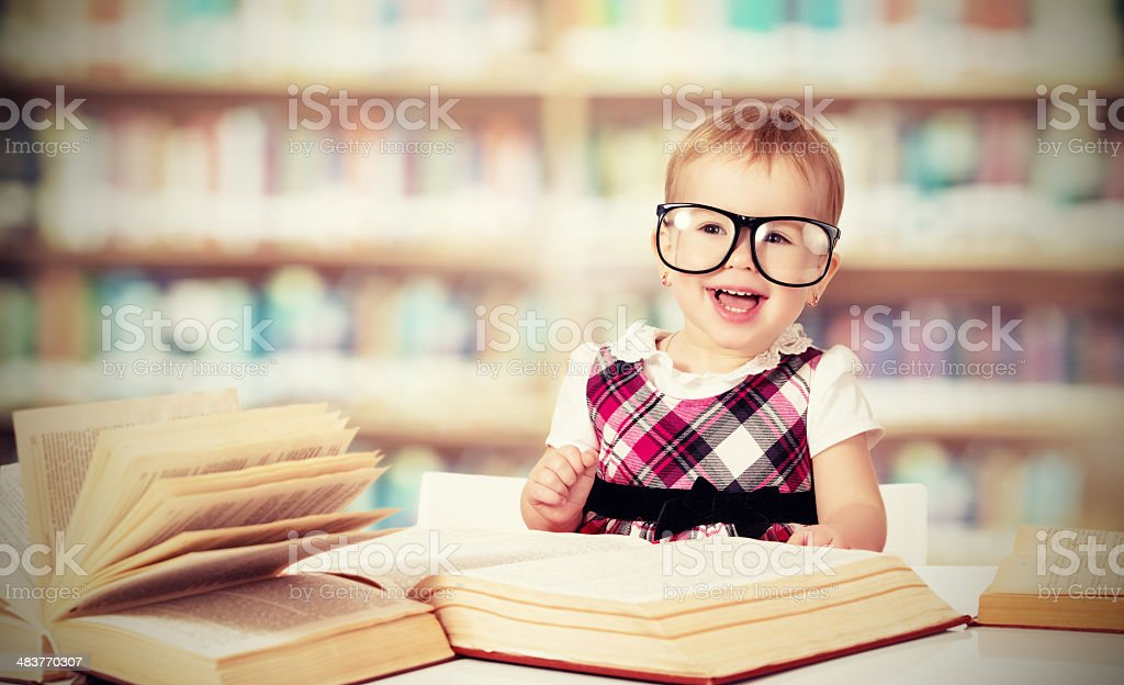funny baby girl in glasses reading a book stock photo