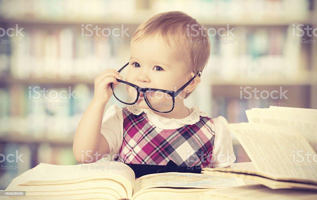 funny baby girl in glasses reading  book stock photo