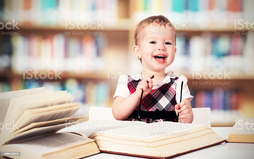 funny baby girl in glasses reading book royalty-free stock photo