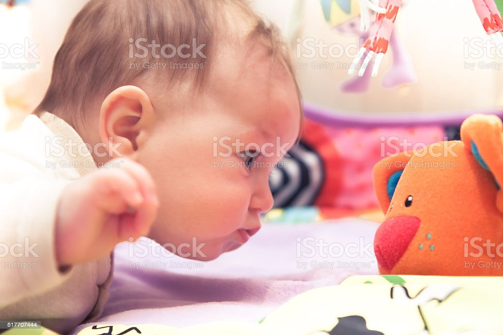 Funny baby playing with toy stock photo