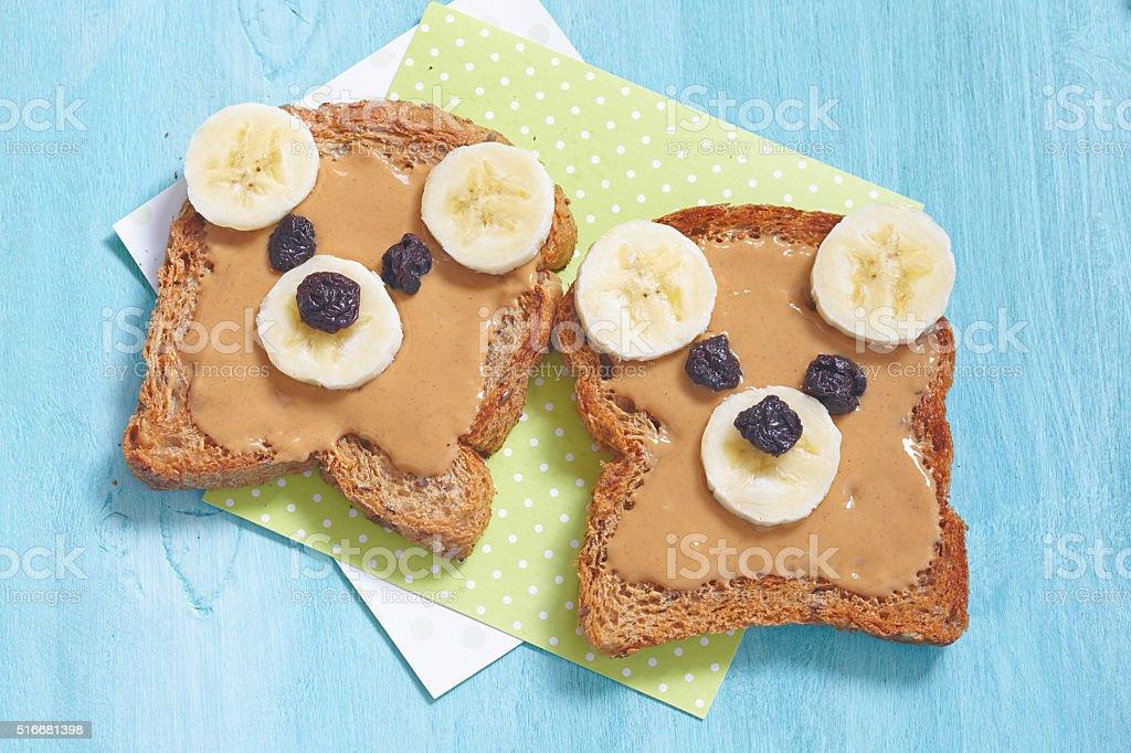 Funny bear face sandwich with peanut butter, banana and raisins stock photo