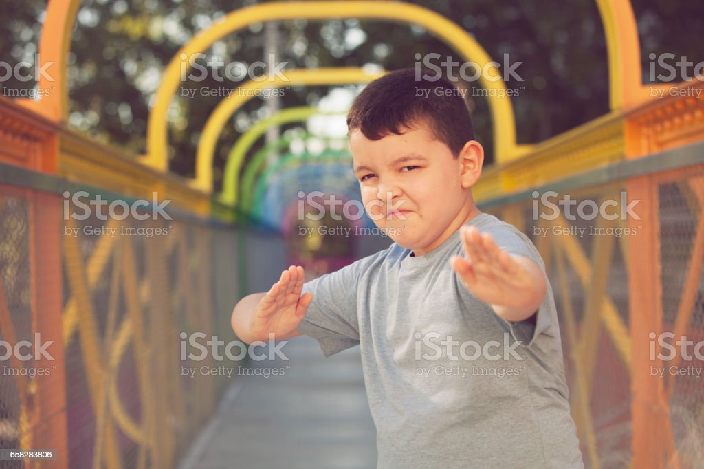 Funny boy doing fight moves stock photo