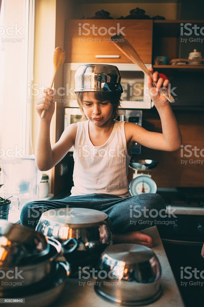 Funny boy playing drums in the kitchen stock photo