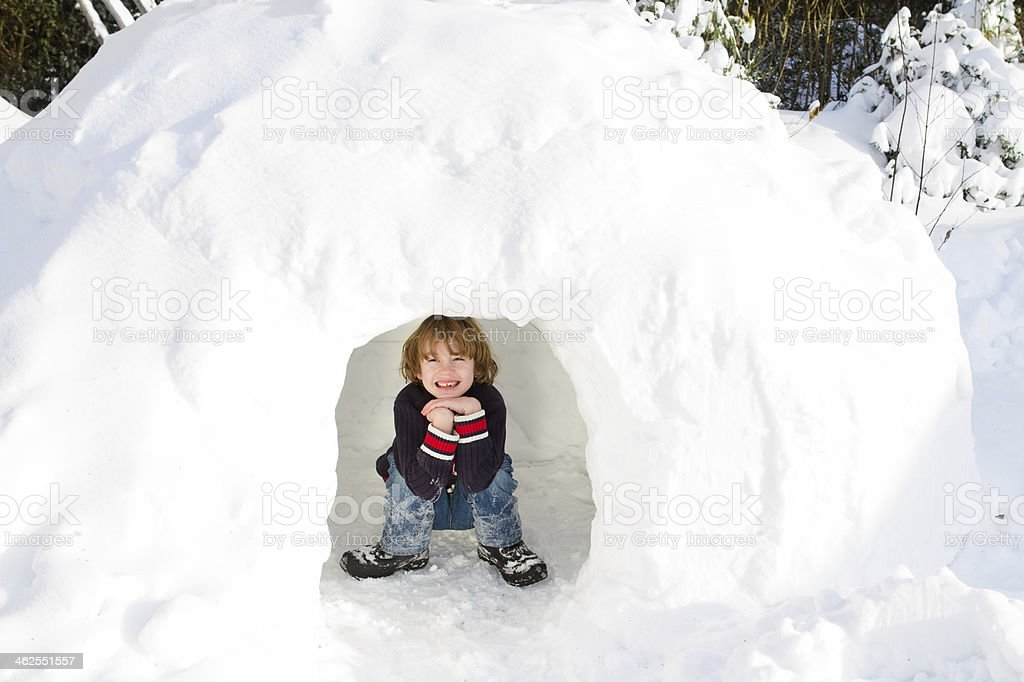 Funny boy playing in a snow igloo stock photo