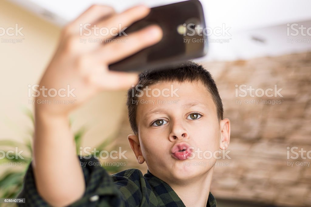 Funny Boy Taking Comic Selfie with Weird Expression stock photo