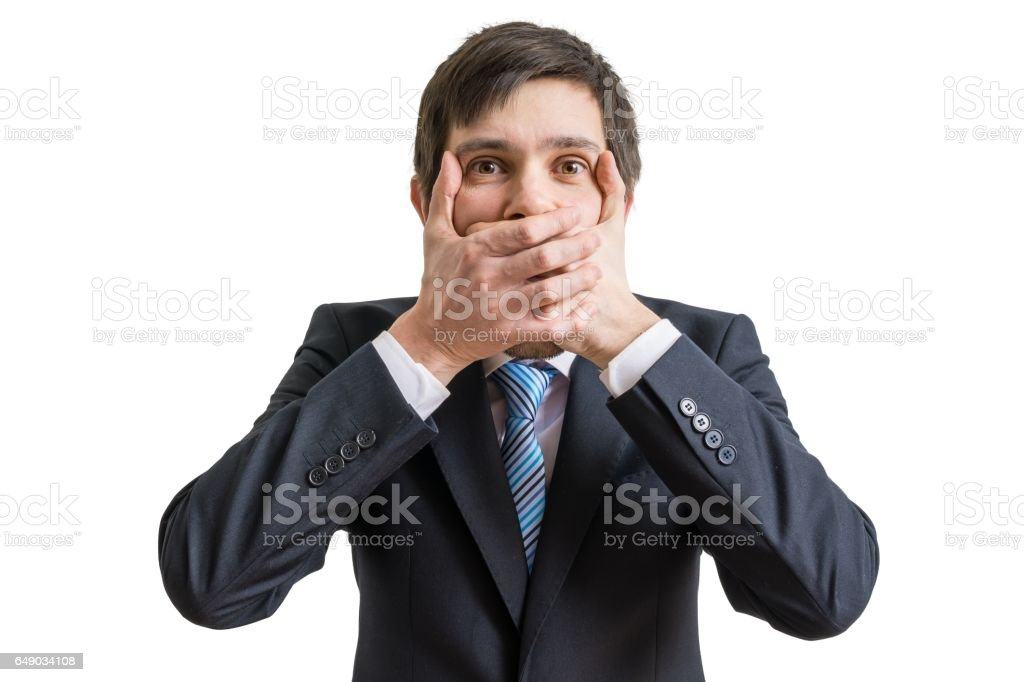Funny businessman is covering his mouth with hands. Isolated on white background. stock photo