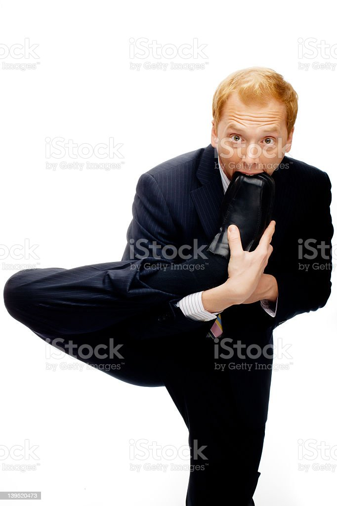 Funny businessman with foot in mouth on White stock photo