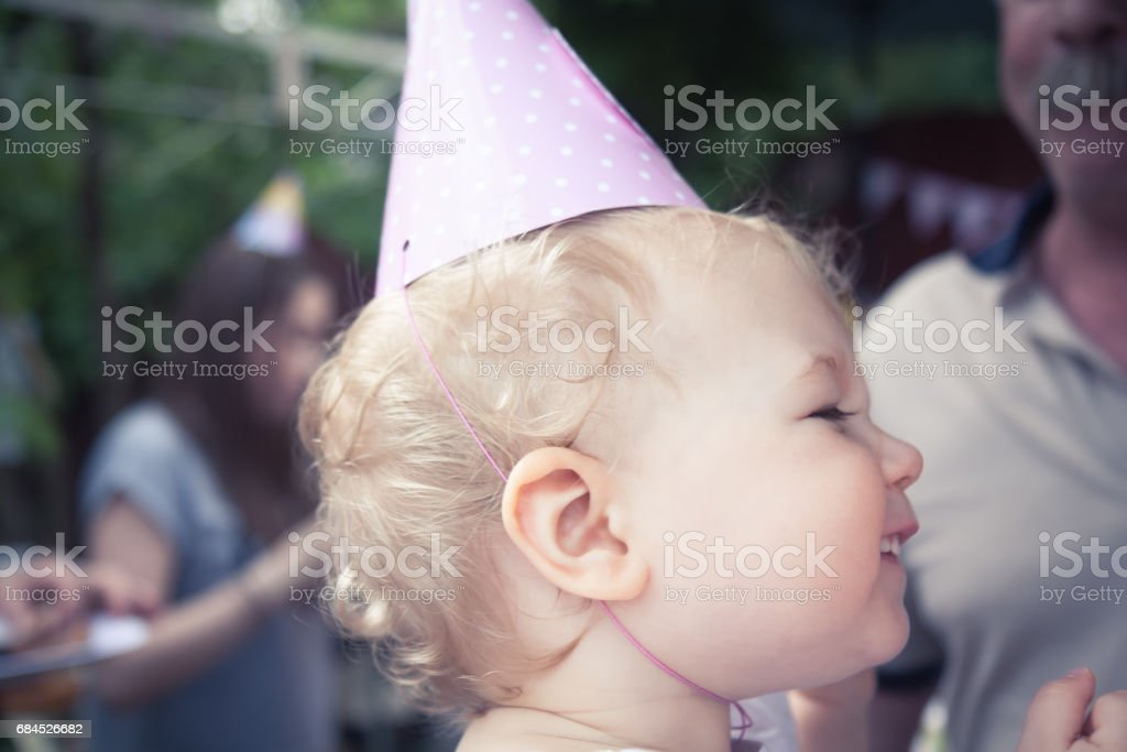 Funny cheerful cute baby girl in birthday cap smiling during birthday party stock photo