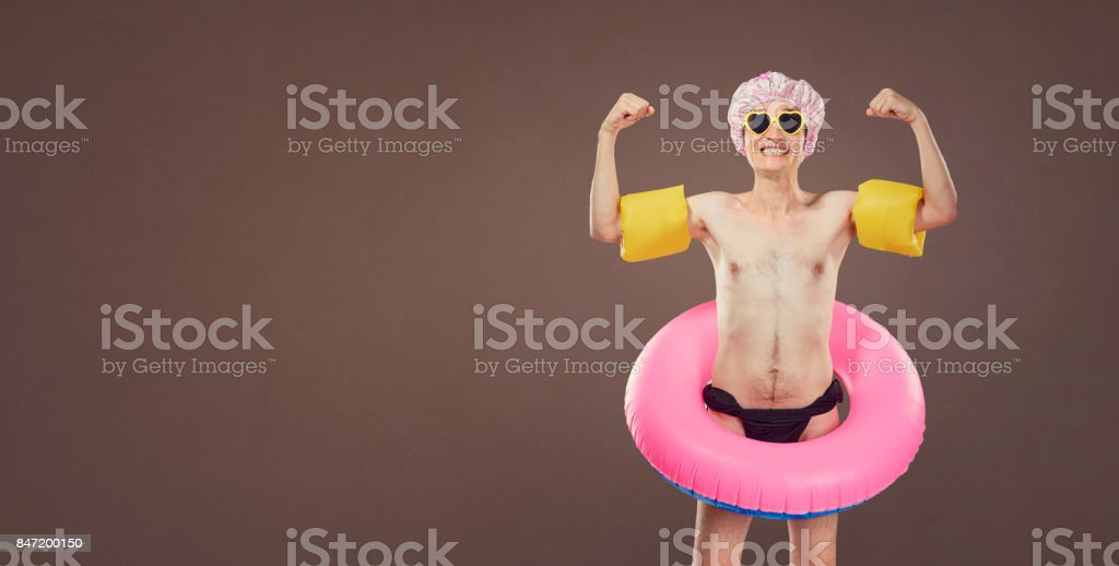 Funny cheerful thin man in a bathing suit with an inflatable cir stock photo