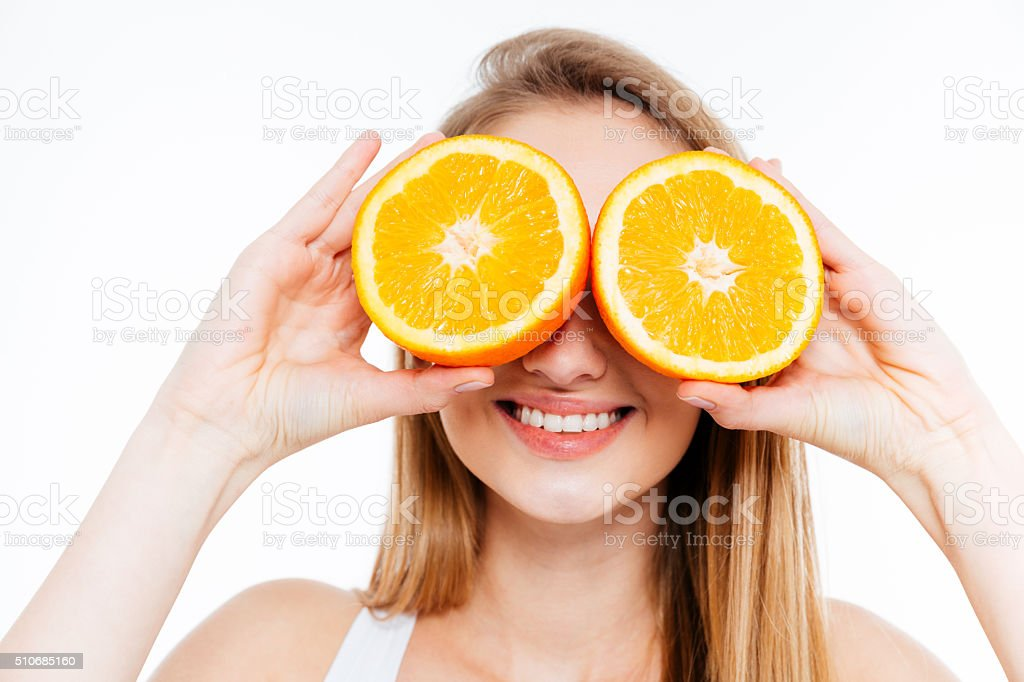 Funny cheerful woman holding two halves of orange agains eyes stock photo