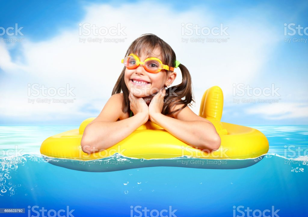 Funny child floating inflatable ring at sea, vacation concept stock photo