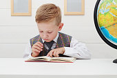 funny Child in school.little boy with Book