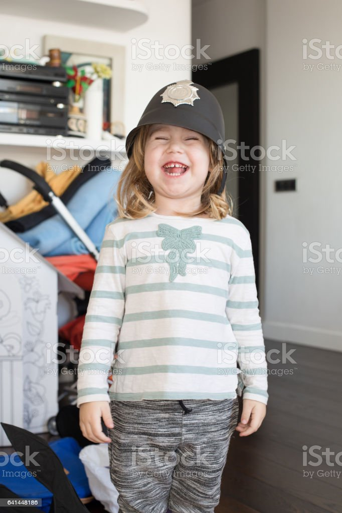 funny child with English Bobby policeman hat laughing stock photo