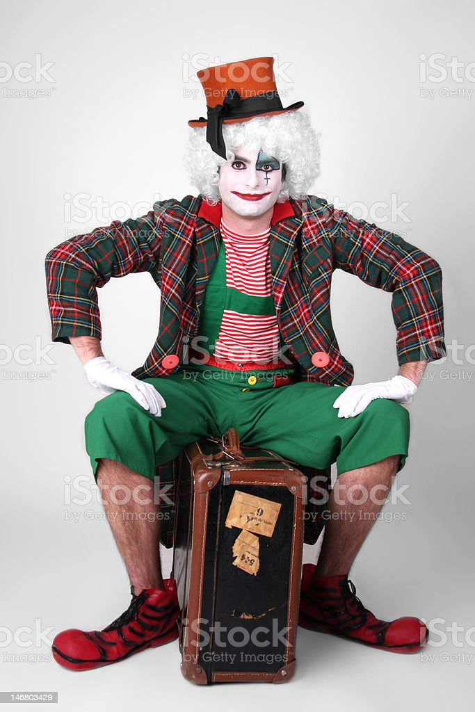 Funny clown sitting on a suitcase royalty-free stock photo