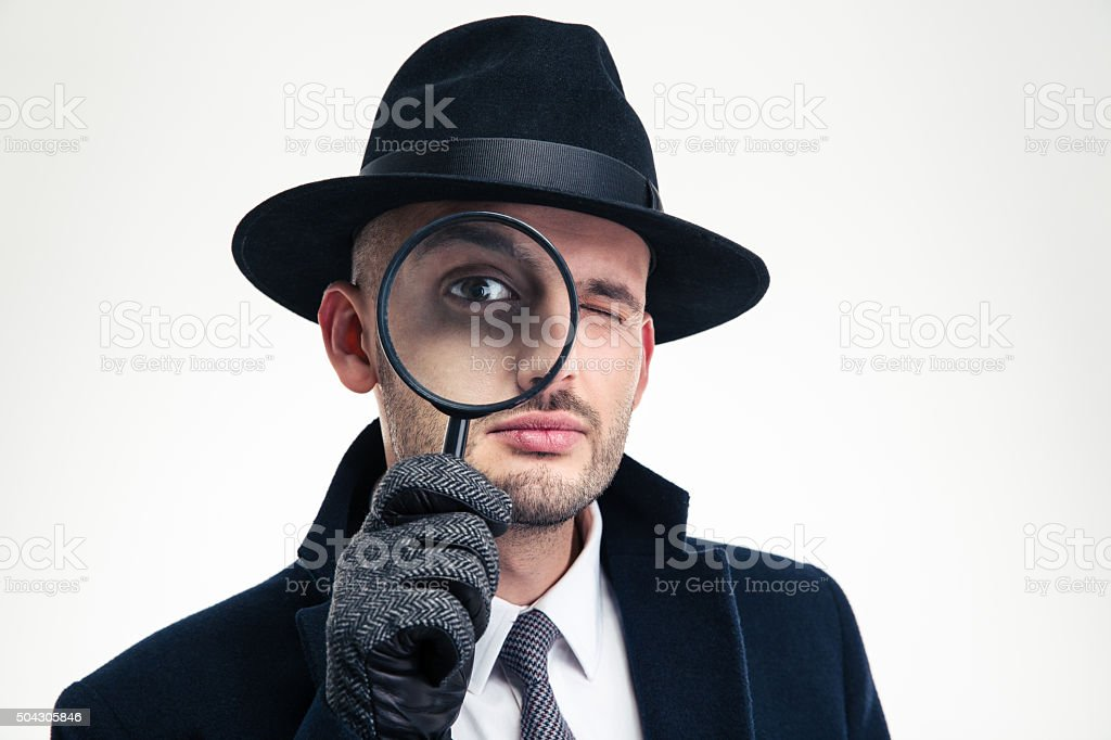 Funny concentrated inspector in black hat looking through the magnifier stock photo