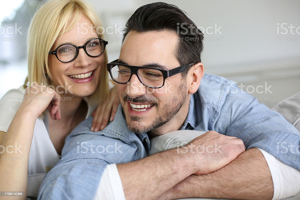 Funny couple with eyeglasses sitting on couch royalty-free stock photo
