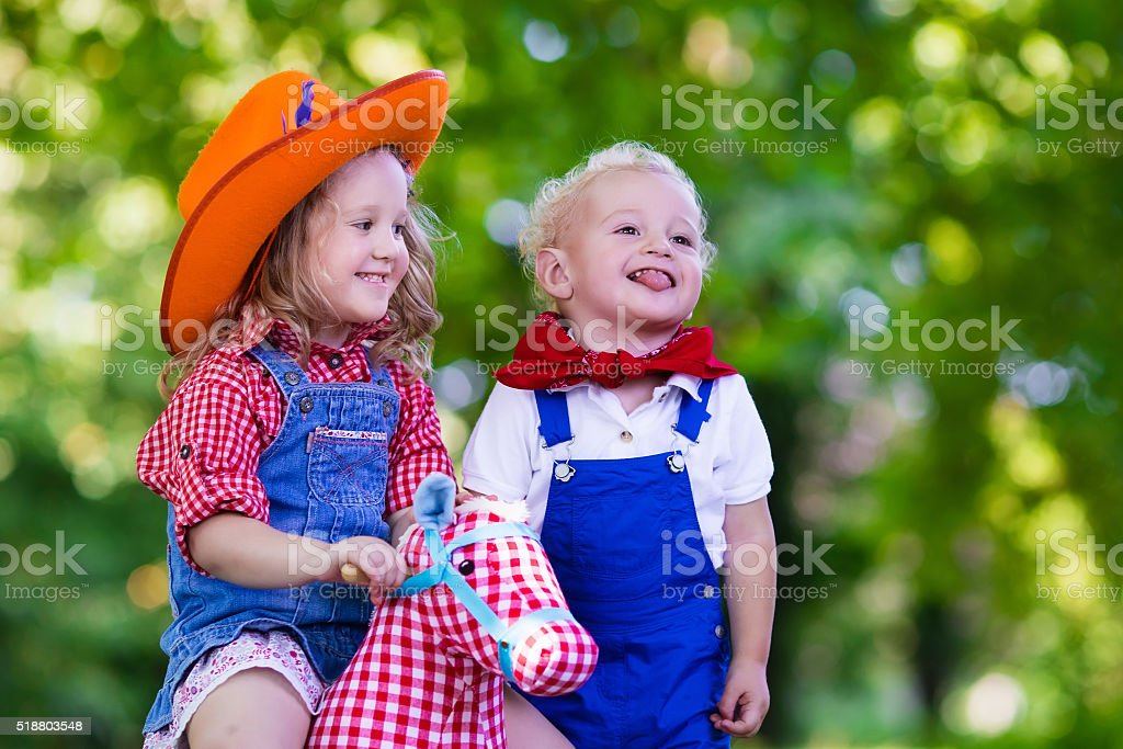 Funny cowboy kids playing with toy horse stock photo