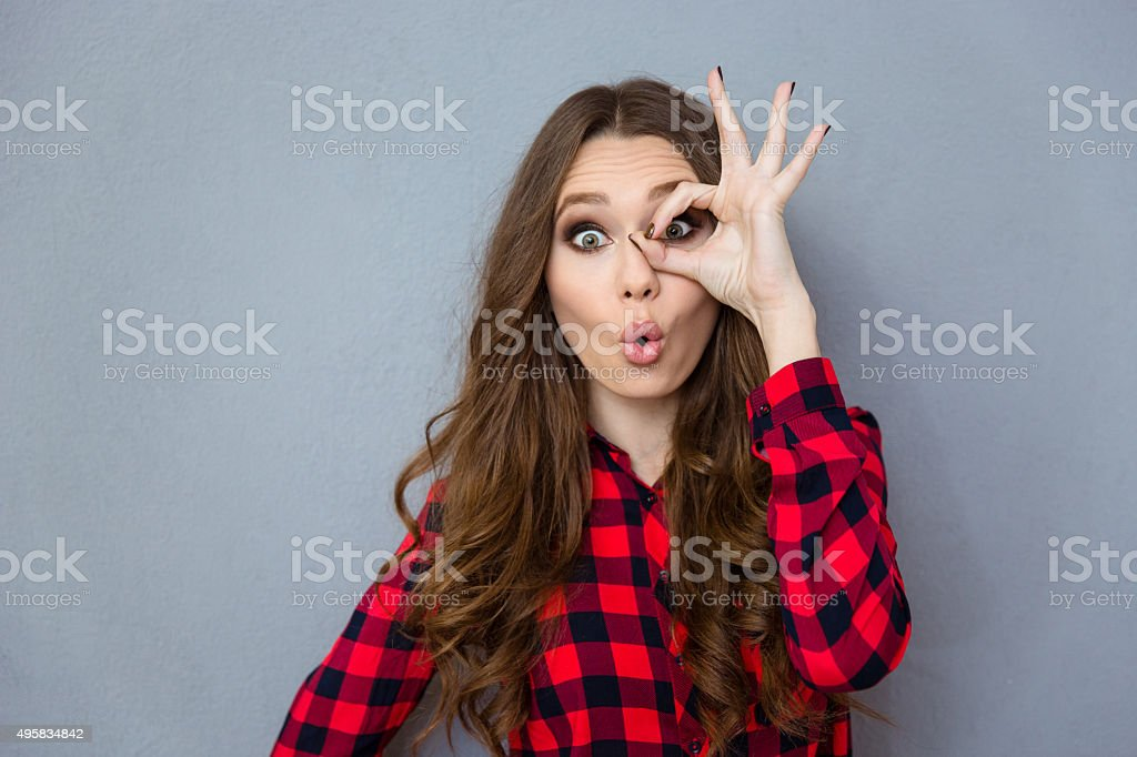 Funny curly girl showing okay gesture near her eye stock photo