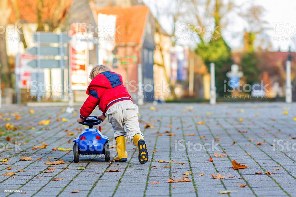 Funny cute child  driving blue toy car and having f stock photo