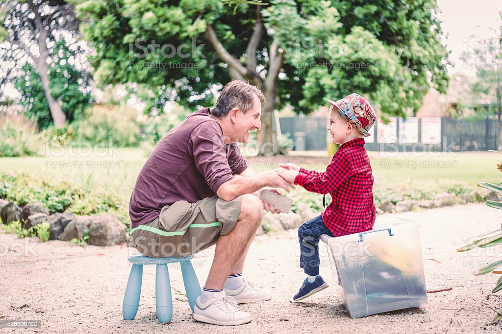 Funny Dad is talking and holding his son hands stock photo