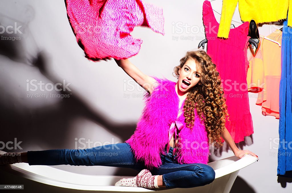 Funny emotional young girl with clothes on bathtub stock photo