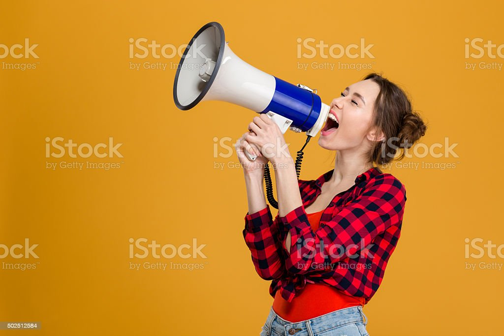 Funny excited young woman shouting in megaphone stock photo