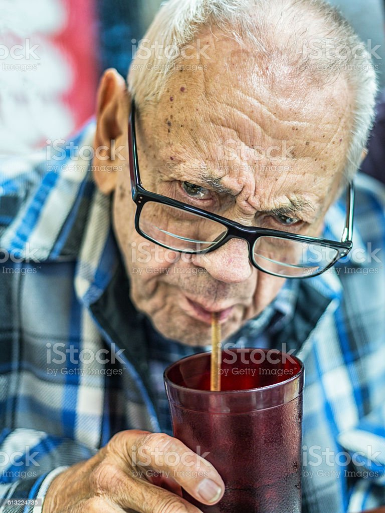 Funny Face 93 Year Old Man Sucking Soda Through Straw stock photo