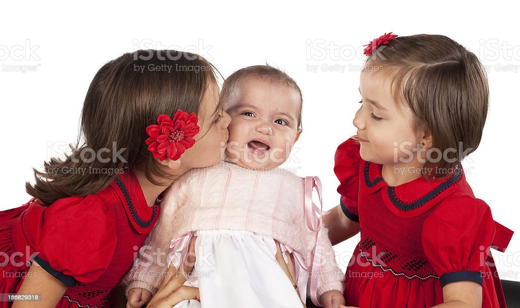 Funny face on baby sister being kissed by her sibling royalty-free stock photo