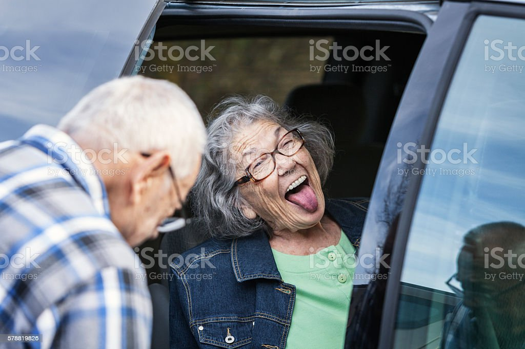 Funny Face Open Mouth Elderly  Senior Woman Sticking Tongue Out stock photo