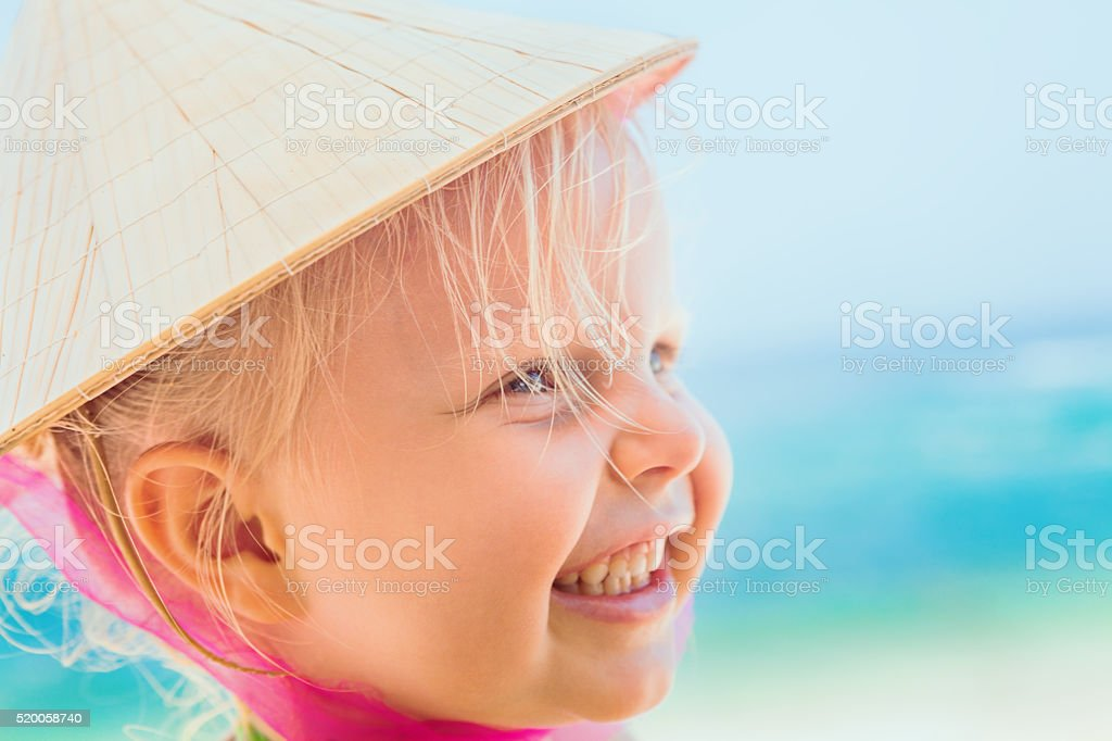 Funny face portrait of happy child in vietnamese straw hat stock photo