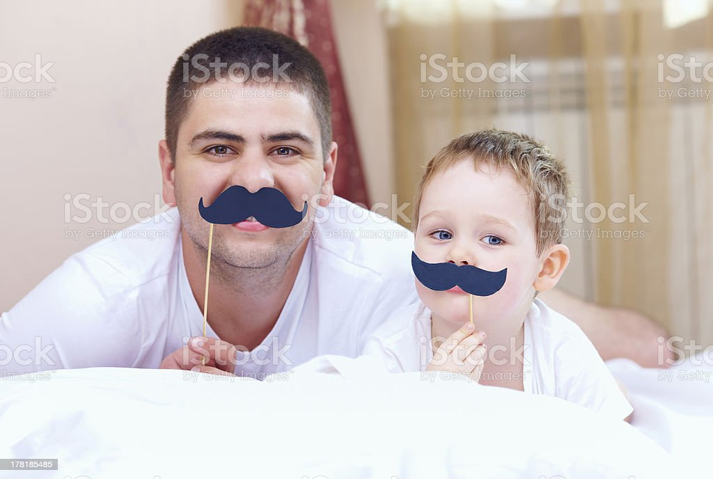 funny father and son with false mustaches, playing at home stock photo
