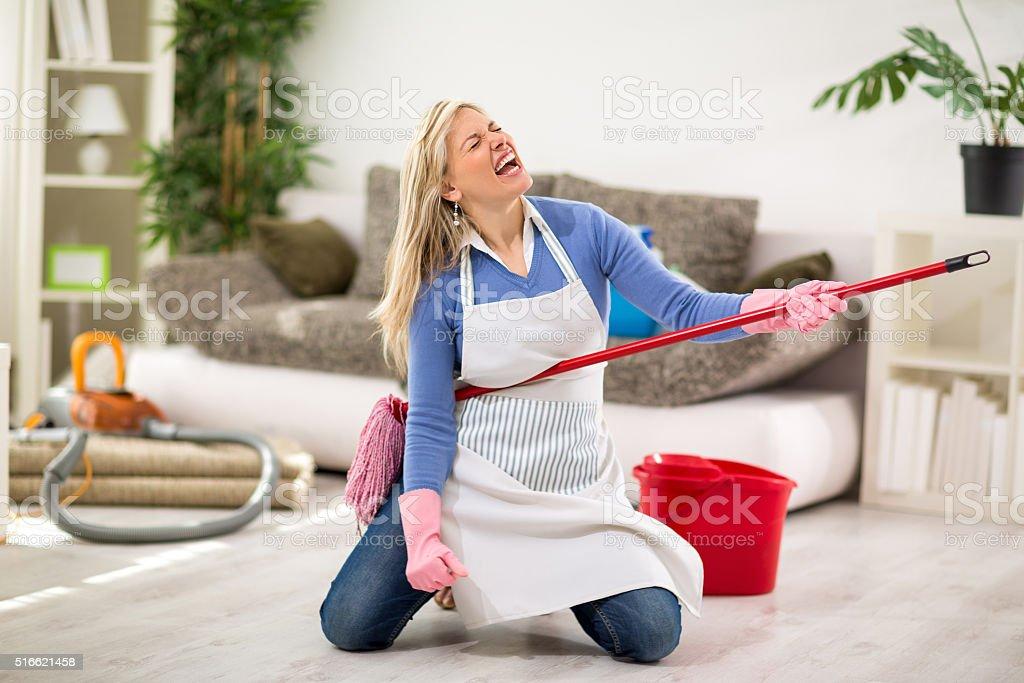 Funny female make joke while cleaning house stock photo