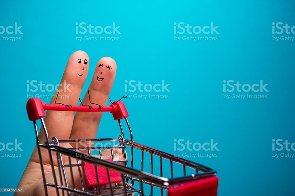Funny fingers shopping at supermarket with red cart trolley on stock photo