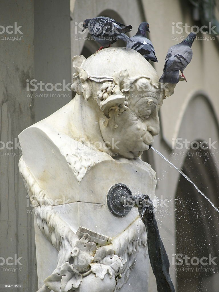 Funny fountain. The man spat by water. stock photo