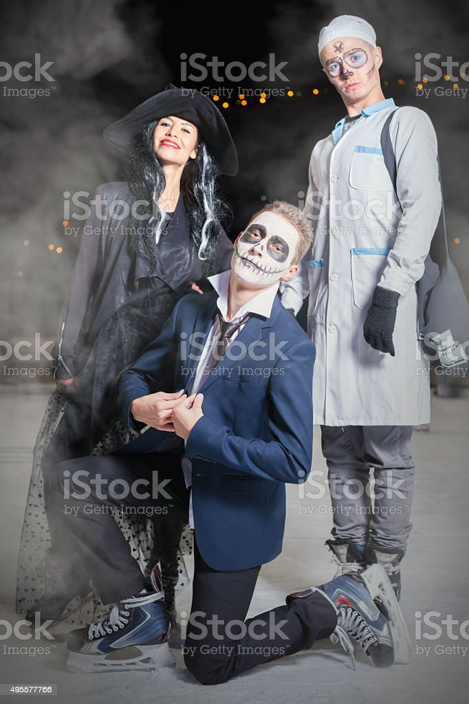 Funny friends group of people ice skating with Halloween horror stock photo