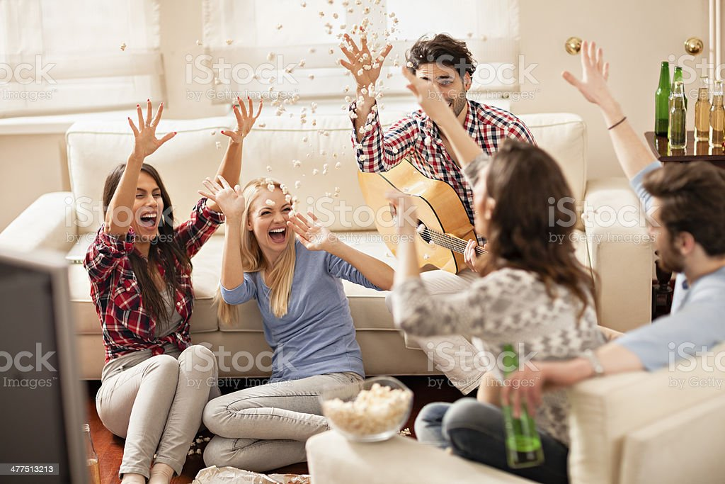 Funny friends throwing popcorn stock photo