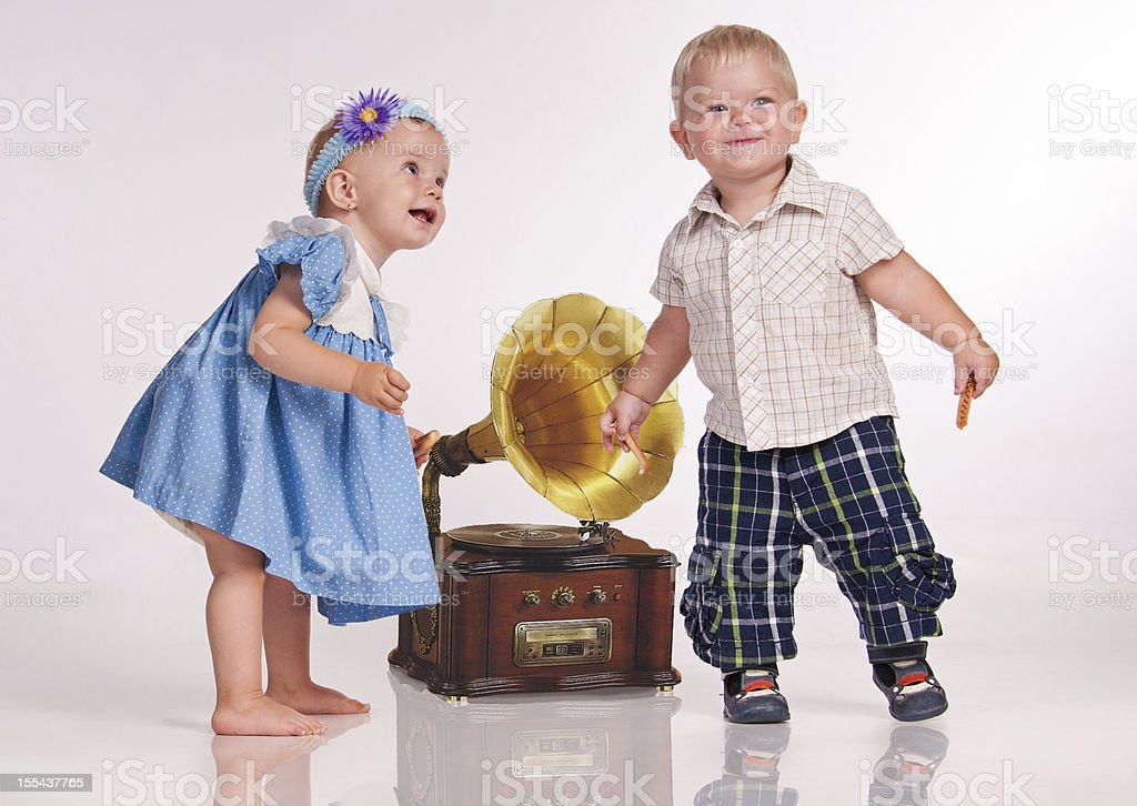 Funny girl and a boy dancing near the gramophone. royalty-free stock photo