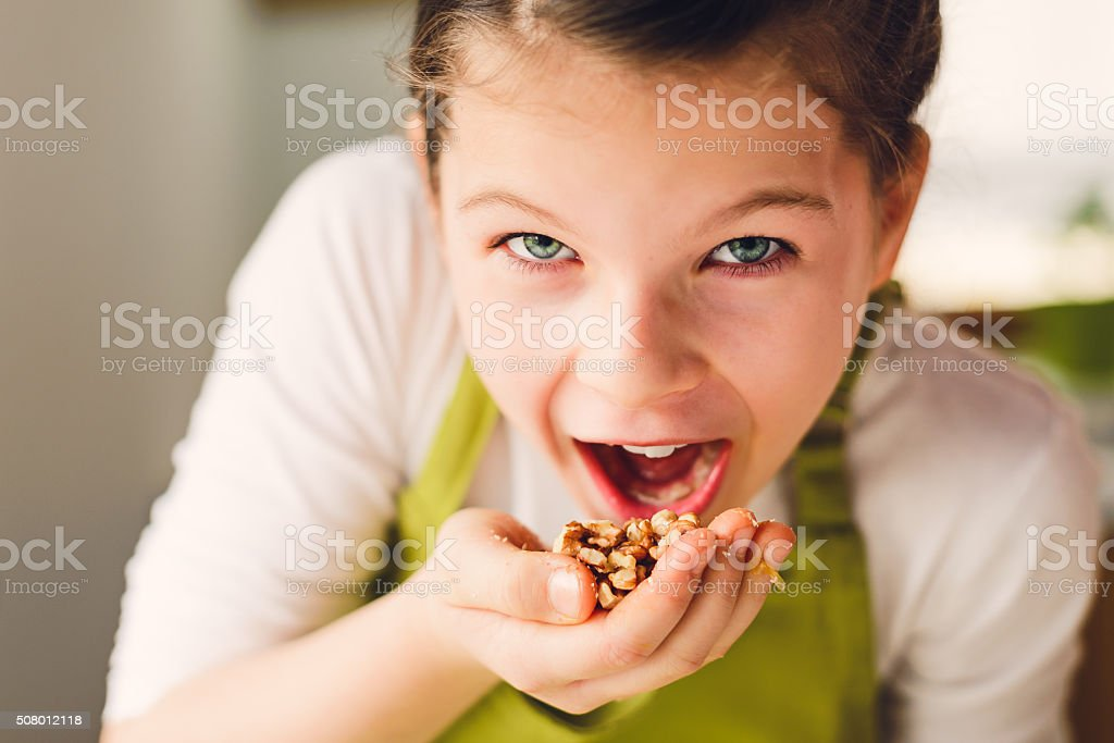 Funny Girl eating walnuts stock photo